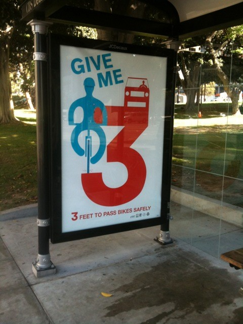 GIVE ME 3's first official poster, at the bus stop at 1st & Main